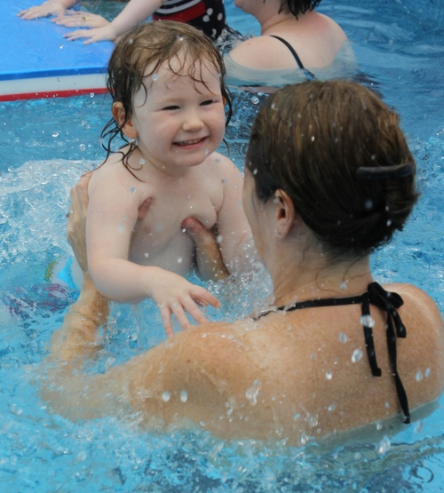 child learning to swim with mum